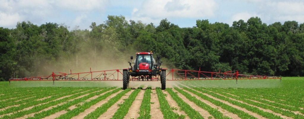 Pesticide being applied to an agronomic crop